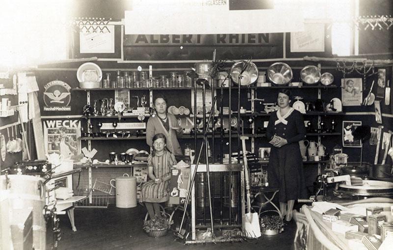 Stand der Firma Rhien in der Turnhalle, Postkarte 1933 (Bernd Voigtländer) Unter den Ausstellern befand sich die Eisenwarenhandlung von Albert Rhien. Links im Bild Martha Rhien mit ihrer Tochter Elfriede.