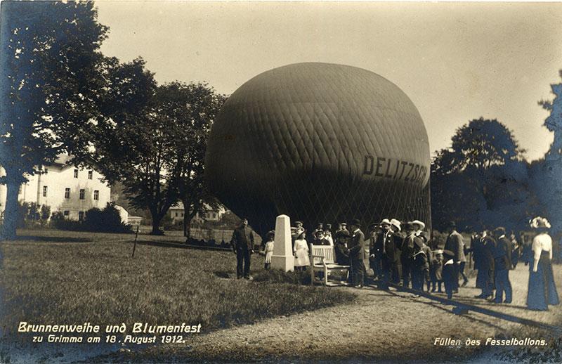 Füllen des Fesselballons Delitzsch, Postkarte 1912 (Kreismuseum). Anlässlich der Brunnenweihe fanden 1912 auch Fesselballonaufstiege statt. Links auf dem Bild ist Kurt Held zu erkennen, der als erfahrener Ballonführer die Aufstiege leitete.